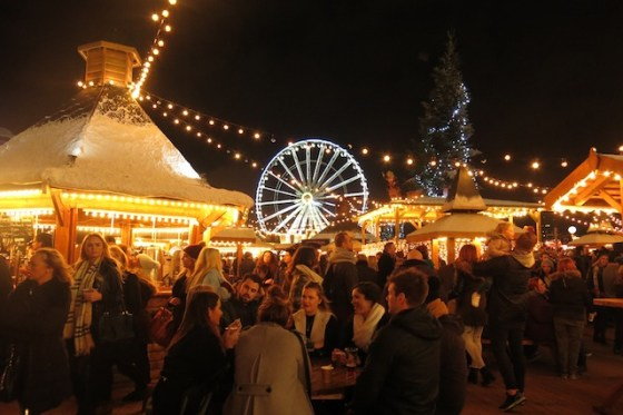 Crowds gather around festively-illuminated food and drink stands at London's Hyde Park Winter Wonderland.