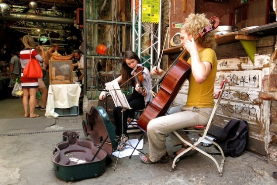 A stringed duo plays for shoppers at Szimpla Kert ruin pub, which transforms into a farmer's market on Sunday mornings.