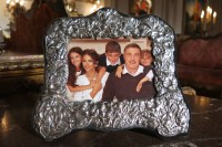 """silver-framed family portrait of the cast of """"The Royals."""" It's in the Great Hall on the London set of the E! television series"""