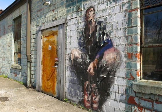 A peeling mural of a crouching man guards the entrance to a doorway on the old James E. Pepper Distillery campus in Lexington, Kentucky.