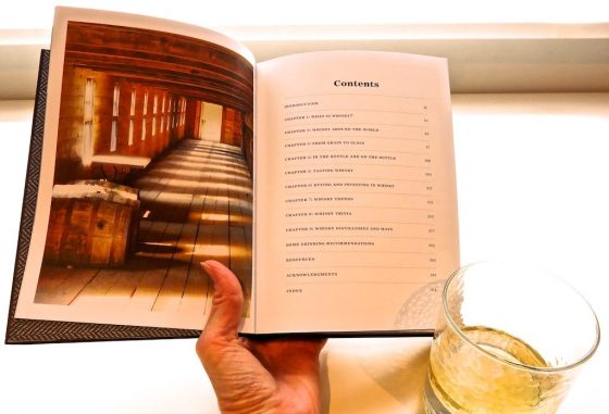 Reading a book about whisky while drinking a dram of Scotch
