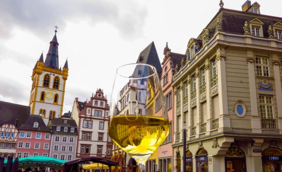 glass of white wine on historic square in Trier, Germany