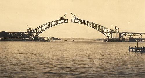 The bridge over Sydney Harbor while under construction, uploaded by Flickr user gramarye.