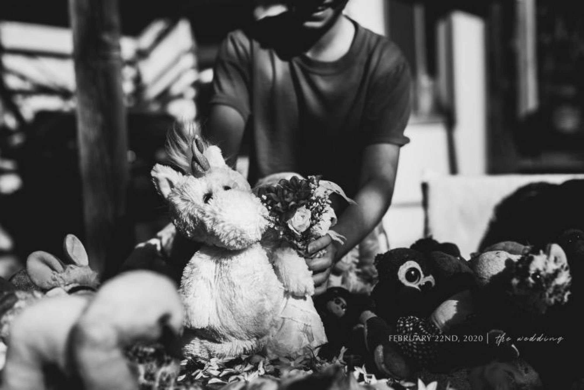 Black and white photo of stuffed animal in a wedding