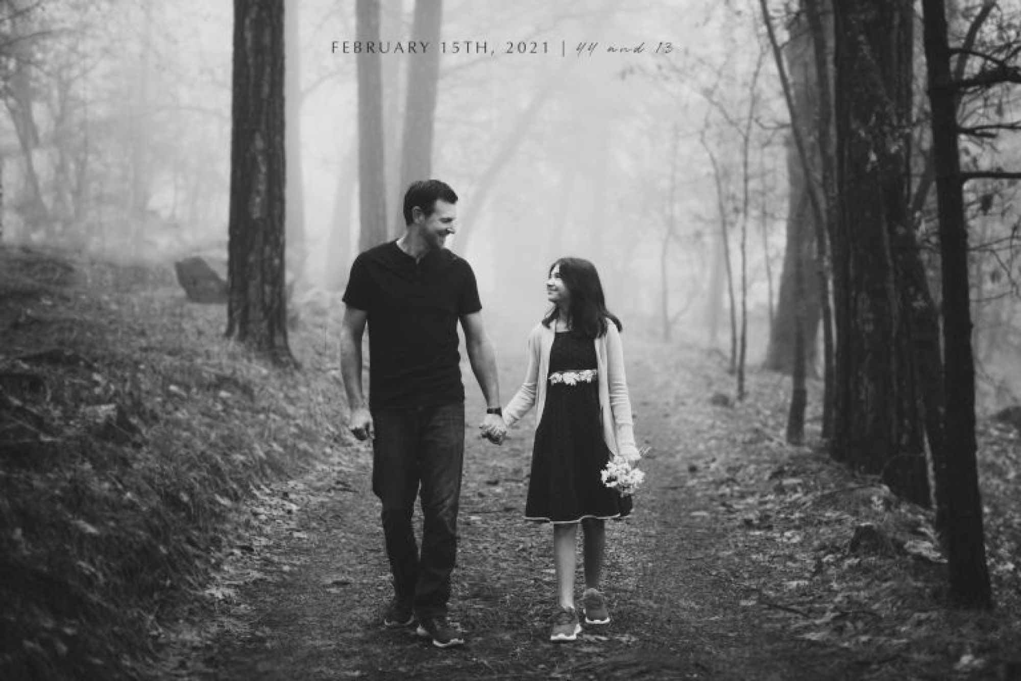 father and daughter walking hand in hand down a path in the woods black and white