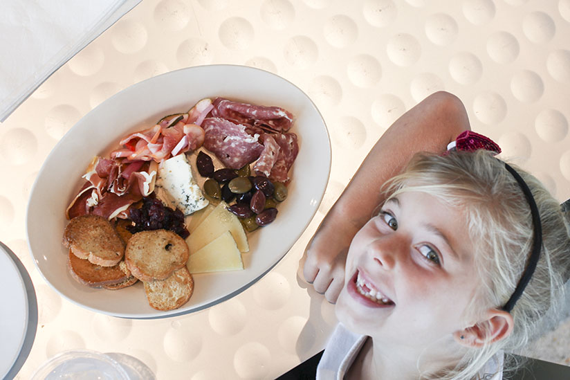 Little girl smiles with charcuterie board