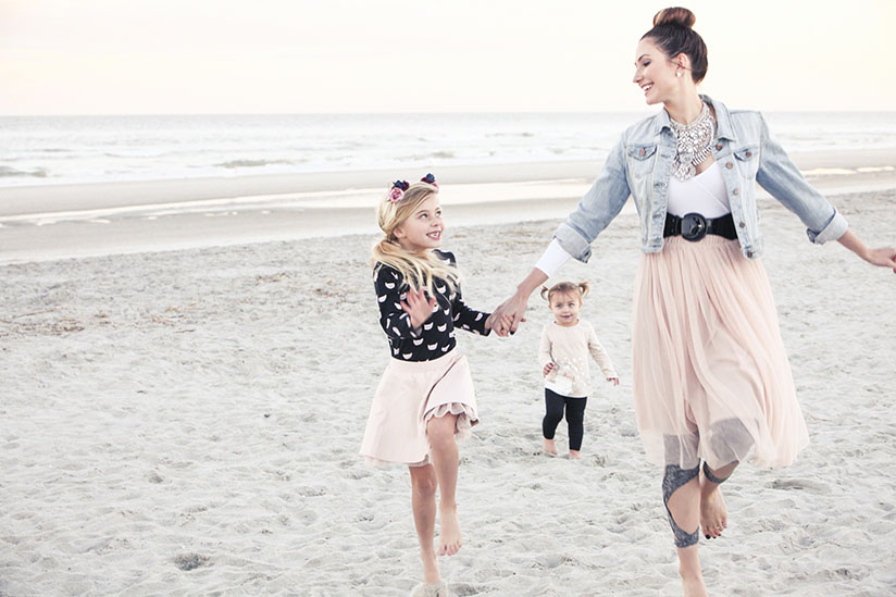 Amy West and daughters play on the beach