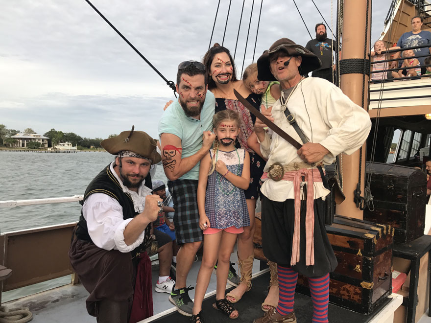 Amy West and family pose with pirates aboard the Black Raven Pirate Ship