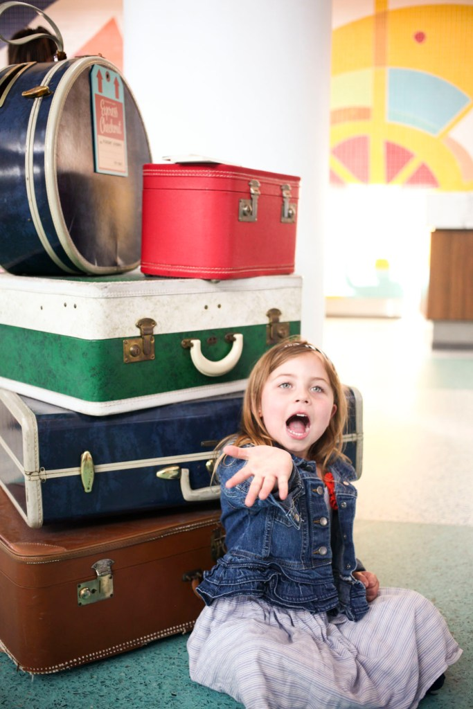 A little girl blows a kiss next to a stack of vintage suitcases