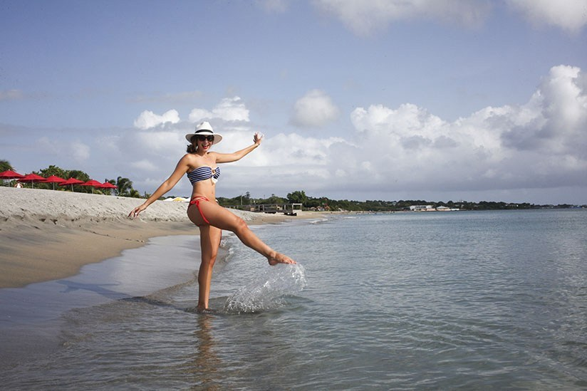 Woman splashes on the beach in Nevis