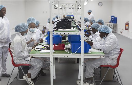 In this Dec. 19, 2013 photo, technicians assemble Android Surtab tablets at the Industrial Park in Port-au-Prince, Haiti. Two tech companies in Haiti have launched competing businesses to sell Android tablets. Startups Surtab SA and Handxom SA began production last month and plan to sell the 7-inch touchscreen devices to phone stores nationwide and markets overseas. (AP Photo/Dieu Nalio Chery)