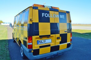 "Van with ""Follow Me"" on back."