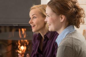 Two happy women sitting by a fire.