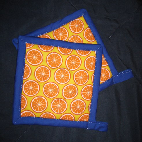 Photograph of hot pads made from a fabric featuring cross-sections of oranges, bound in cobalt blue