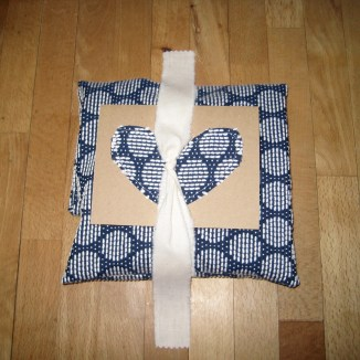 Wrapped gift with card on top, tied up with a strip of muslin