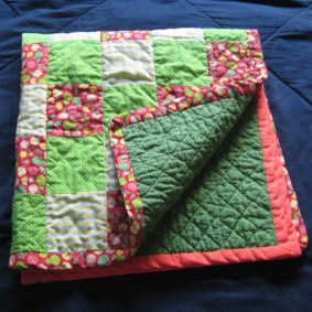 Photograph of folded baby quilt showing front of pieced squares (green, yellow, and red), red binding, and green backing