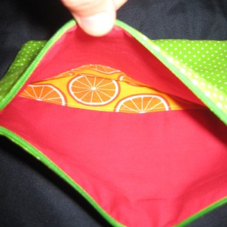 Photograph of green polka dot zip pouch showing pieced interior of red and a printed yellow and orange fabric featuring cross-sections of oranges