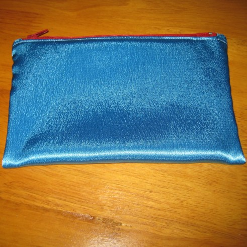 Photograph of a sky blue satin pouch with a red zipper on the top edge