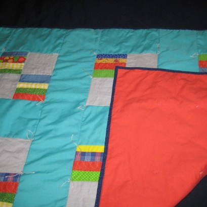 Photograph of aqua and multi-colored baby quilt showing coral-colored back folded over as well as printed dark blue binding