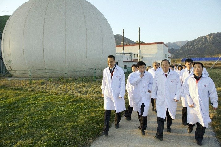 Biogas used in China with a biogas holder in the background.