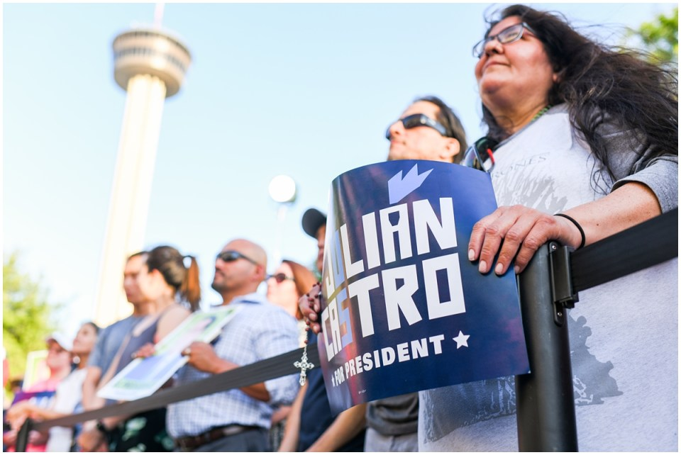 Julian Castro supporter holds blue sign during rally in front of The Tower of the Americas in San Antonio, TX