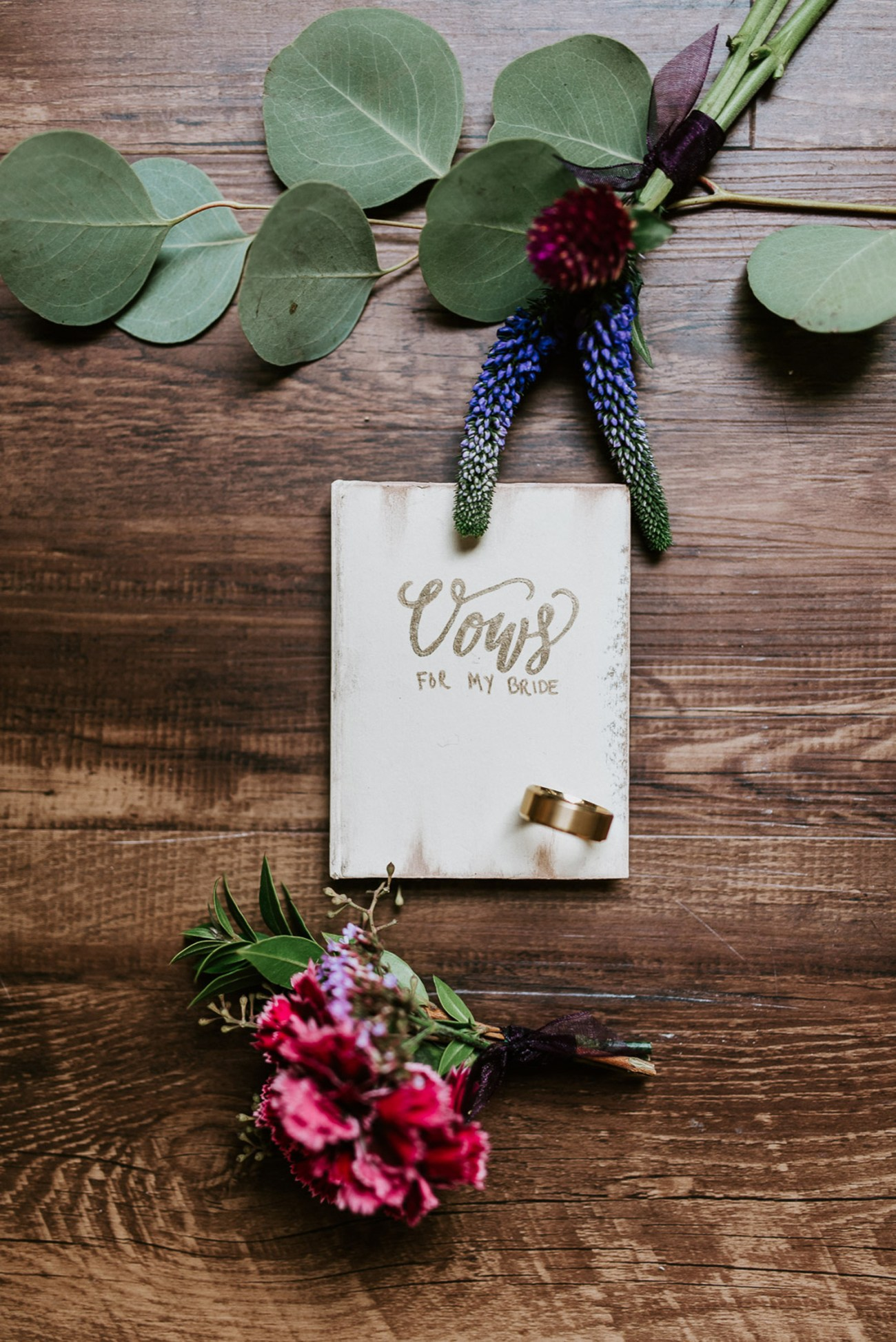 Personalized vow book and groom details on wedding day, boutonniere details