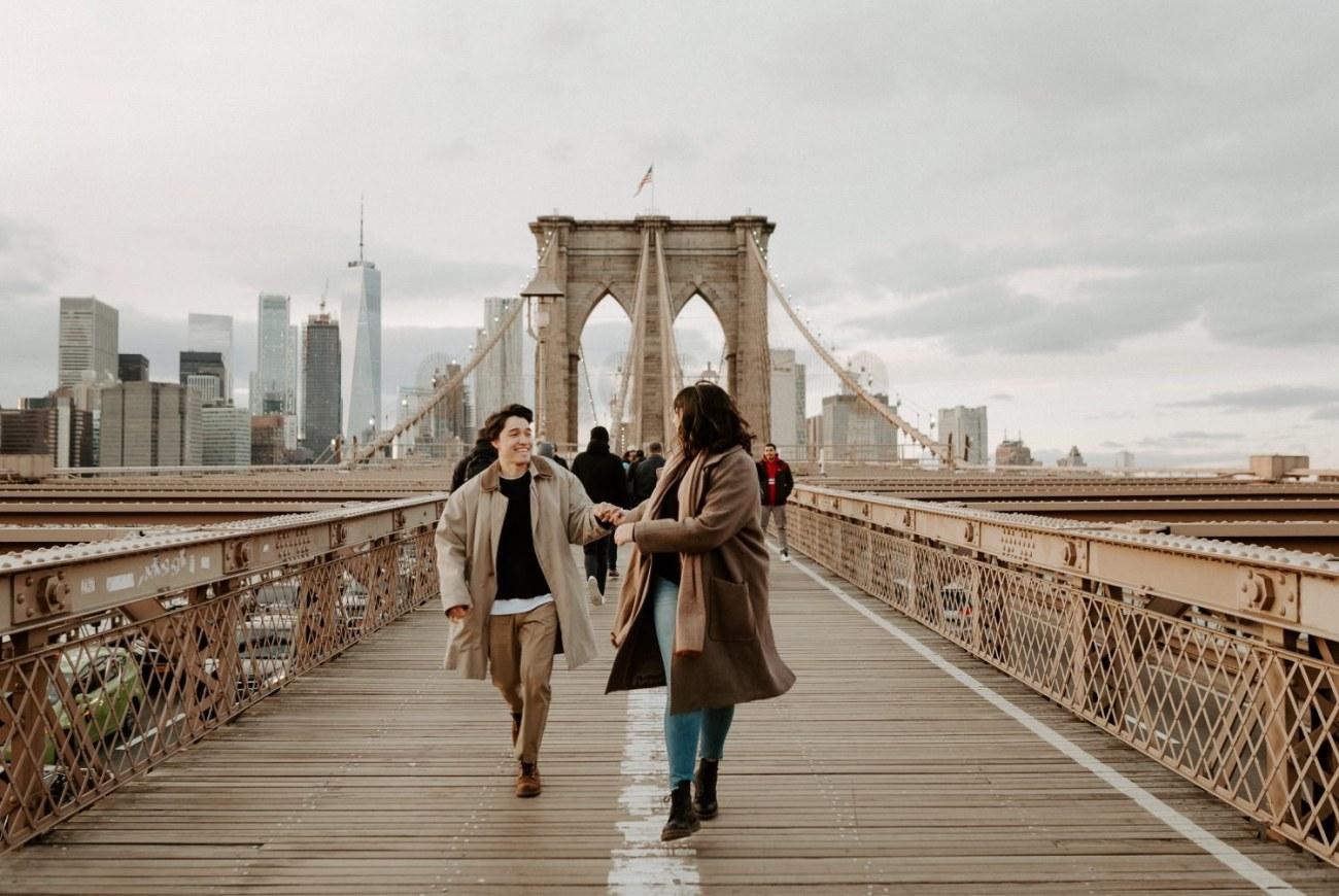 Couple running on the Brooklyn Bridge at sunset, Couple session photos for sunset on the Brooklyn Bridge