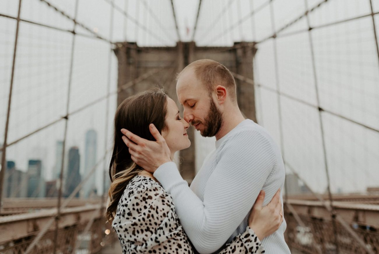Couple standing on the Brooklyn Bridge for their engagement photos