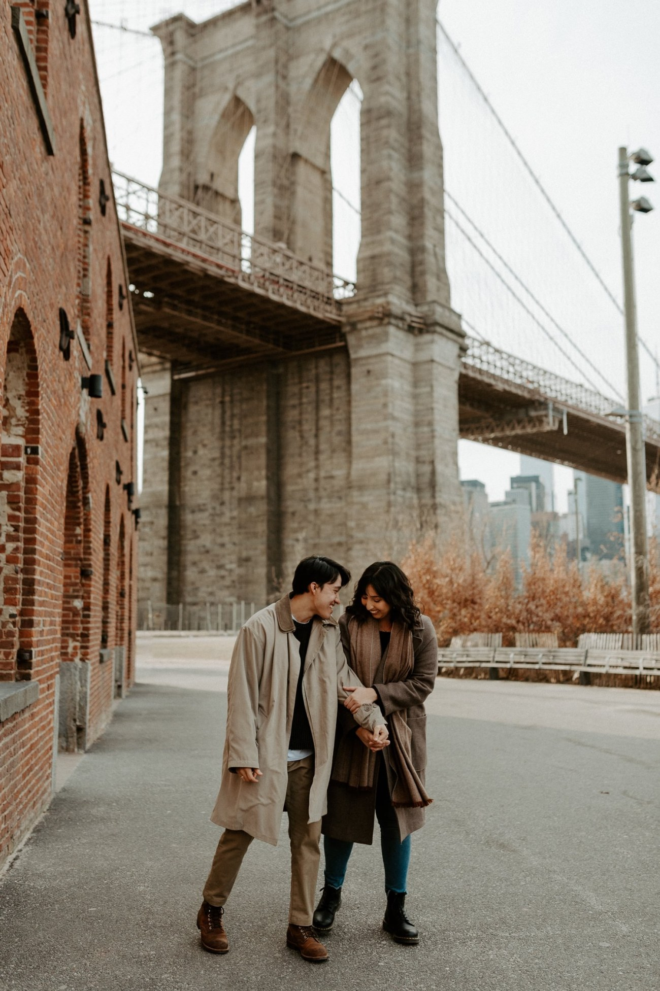 Couple walking by the Brooklyn Bridge and Ann's warehouse in Dumbo Brooklyn