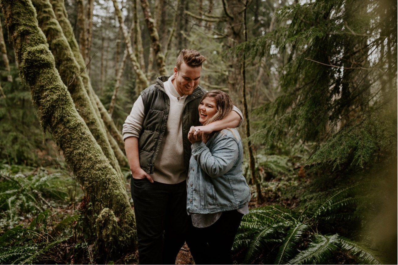 Couple walking under the rain in Mt Hood National Forest for their Engagement Photos. Bend Wedding Photographer. Anais Possamai Photography