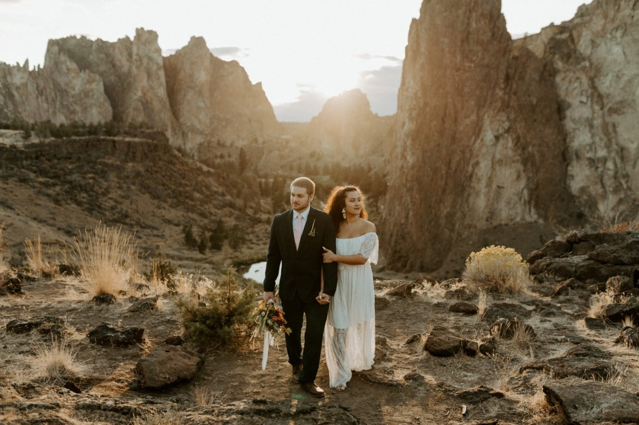 Bride and Groom walking at top of Smith Rock State Park. Anais Possamai Photography Bend wedding photographer