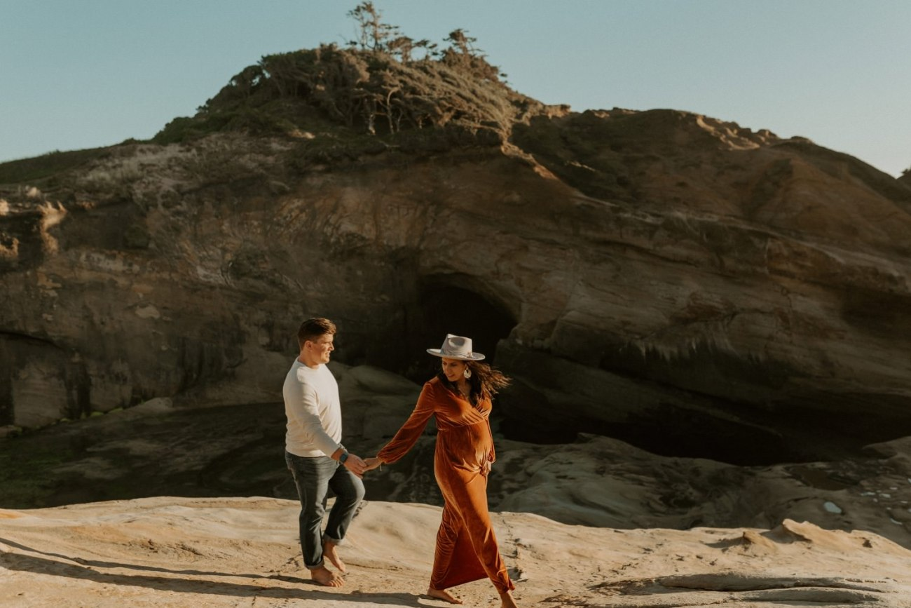 Couple walking on the beach in Cape Kiwanda Pacific City Oregon for their maternity Session