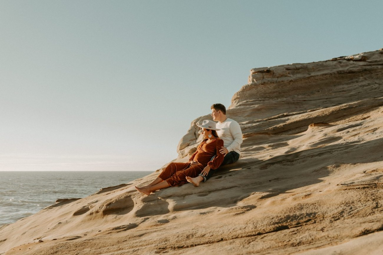 Couple seating on the beach in Cape Kiwanda Pacific City Oregon for their maternity Session