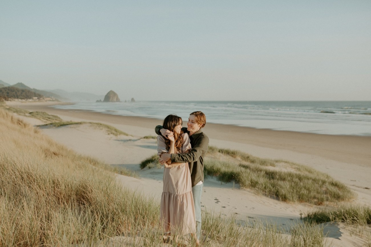 Couple standing in the high grass on Cannon Beach for their engagement session