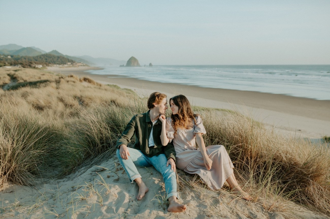 Couple sitting on the beach at Cannon Beach in Oregon