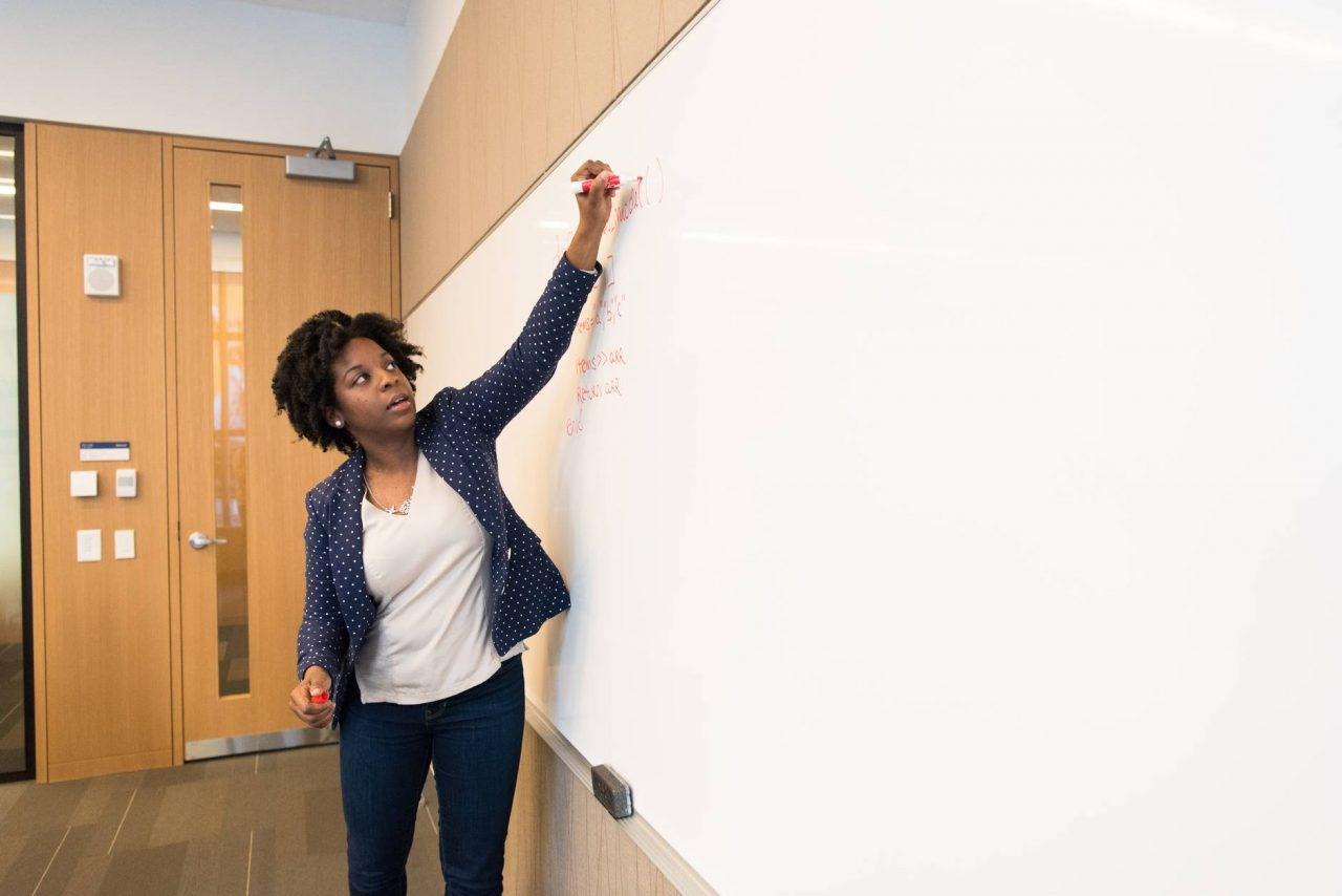 woman writing on dry erase board