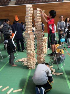 椅子の上に上がって、積木を高く積み上げる様子