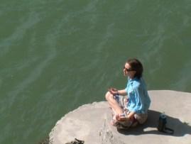 girl meditating by river
