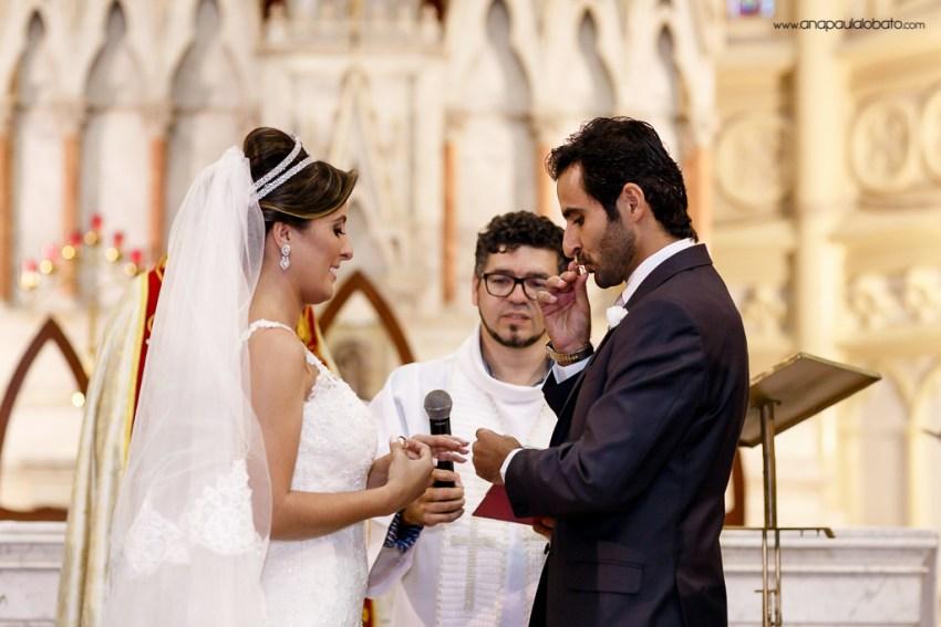 Noivo beija aliança da noiva no altar