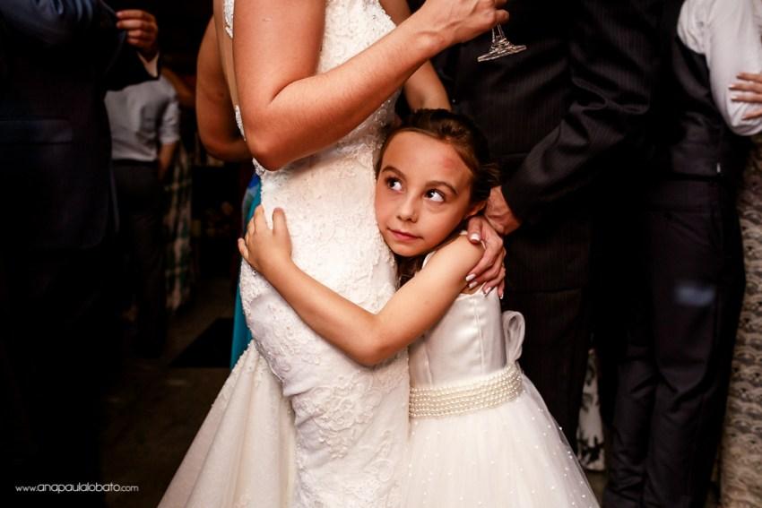 Daminha fofa abraça a noiva em seu casamento
