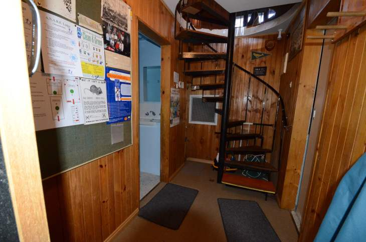 ANARE Ski Club - Notice board, bathrooms left and right and staires up to living area.