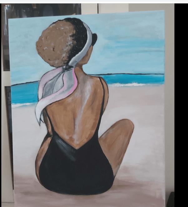 Paisible. Une femme assise sur la plage regardant vers le rivage. Everybody's hurt.