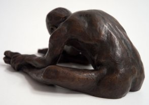 sinister lateral dorsal view of a bronze sculpture of a male nude sitting with his head on his knee