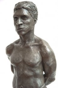 frontal lateral view of bust of bronze sculpture of male nude standing figure