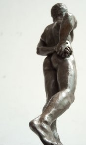 caudal dorsal lateral view of bronze sculpture of standing male nude figure