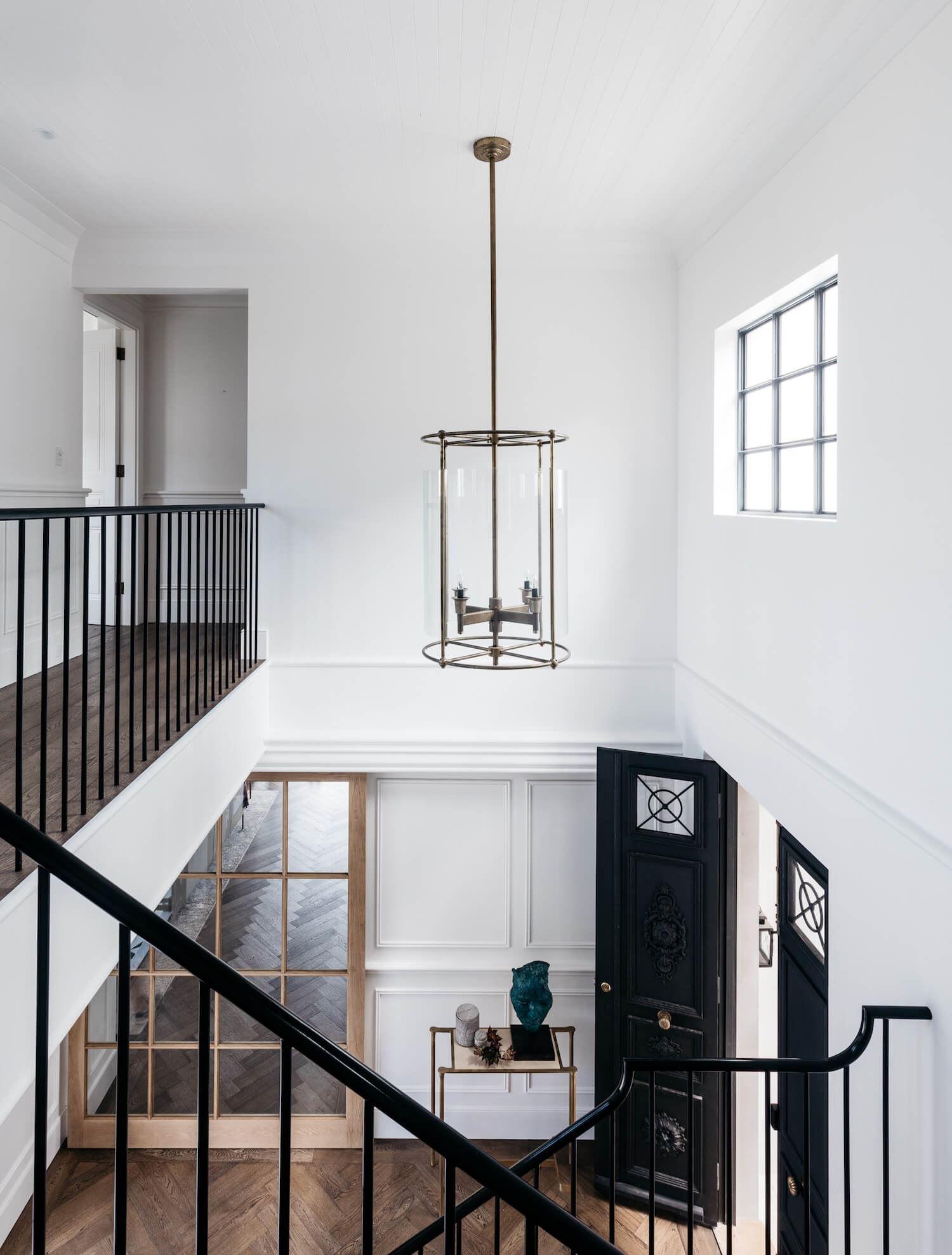 Zona de escalera y entra planta de estilo francés minimalista