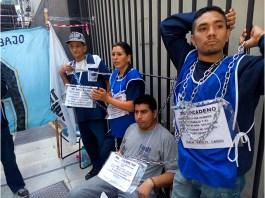 Trabajadores de maestranza tercerizados encadenados al Ministerio de Trabajo en reclamo del cobro de sueldos adeudados.