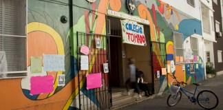 """Se ve la fachada del Liceo número 9 Santiago Derqui, arriba de la puerta de entrada una bandera en la que se lee: """"Colegio Tomado"""""""