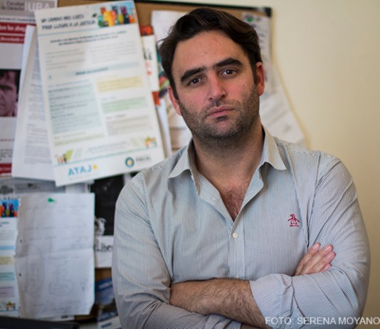 Julián Axat, poeta y titular de la Dirección General de Acceso a la Justicia, está parado de frente, con los brazos cruzados y mirada seria.