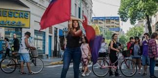 Una mujer flamea unas banderas propias de una murga. Está parada sobre la calle donde también caminan otras personas. De fondo, se puede observar La Bombonera, estadio de Boca Juniors.